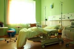 Ein Krankenhauszimmer mit einem Bett und etwas Ausrüstung Stockfotos
