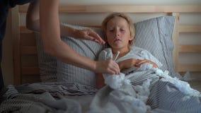Ein kranker kleiner Junge in einem Bett Mutter küsst ihn und misst seine Temperatur Babygrippekonzept stock footage