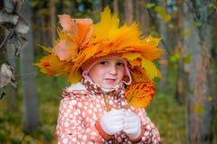 Ein Kranz vom Gelb verlässt auf dem Kopf des Mädchens Herbstporträt eines kleinen Mädchens, das eine Krone von gelben Blättern tr stockfotografie