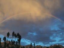 Ein Kreisregenbogen über den Bergen unter den donnernd dunklen Wolken im Himmel nach dem Regen Stockfotografie