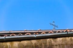 Ein Kreuz auf den Dächern im blauen Himmel Stockfotografie