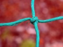Ein Kreuz gemacht von einem verdrehten Seil mit Knoten in der Mitte lizenzfreie stockbilder