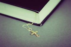 Ein Kreuz mit einer Kette nahe bei einem geschlossenen Buch Lizenzfreies Stockfoto