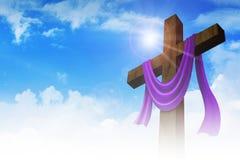 Ein Kreuz mit purpurroter Schärpe auf Wolkenhintergrund Lizenzfreie Stockfotografie