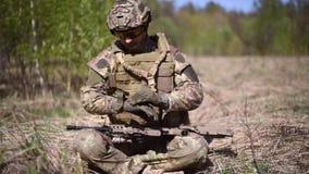Ein Krieger oder ein Militärsoldat, die in der Tarnung gekleidet wurde, statteten aus und trugen Handschuhe und eine Granate stock video