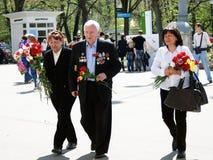 Ein Kriegsveteran geht mit Blumen Lizenzfreie Stockbilder