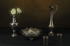 Ein Krug mit einer Schale der Schokolade, des Vase und der Rose auf dem Tisch Lizenzfreies Stockfoto