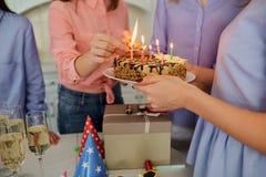 Ein Kuchen mit Kerzen für den Geburtstag in den Händen der Mädchen c Lizenzfreies Stockfoto