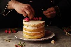 Ein Kuchen mit Rosen und den Händen eines Kochs Lizenzfreies Stockfoto