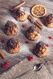 Ein Kuchen mit Schokolade und Kondensmilch auf einem Holztisch mit einer Serviette und einem Löffel Kleine Kuchen Stockbild