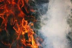 Ein Kulttanz des Feuers und des Rauches gegen einen Hintergrund des grünen Grases Drei Elemente stockfotografie