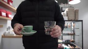 Ein Kunde nimmt die Espressoschale mit Kaffee und einem Glas Wasser zu seinem Tabelle stock video footage