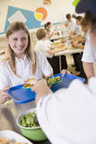 Ein Kursteilnehmer, der das Mittagessen in der Schulecafeteria montiert Lizenzfreie Stockfotos