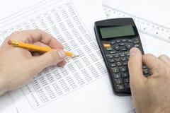 Ein Kursteilnehmer, der seine Matheheimarbeit tut Lizenzfreie Stockbilder
