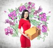 Ein lächelnder Brunette in einem roten Kleid hält eine orange Geschenkbox lizenzfreie abbildung
