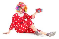 Ein lächelnder Clown auf einem Boden, der ein Geschenk anhält Stockfotografie