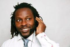 Ein lächelnder Geschäftsmann, der mit dem Kopfhörer, Kundendienst lächelt und nennt Stockfoto