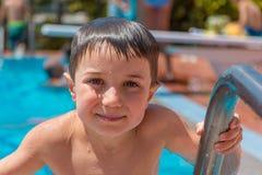 Ein lächelnder Junge (5-6) auf der Leiter eines Swimmingpools lizenzfreie stockfotos