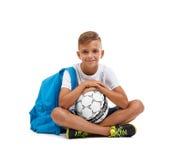 Ein lächelnder Junge mit einem Ball und eine blaue Schultasche, die in einem Yoga sitzt, werfen auf Glückliches Kind lokalisiert  Lizenzfreies Stockbild