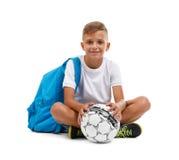 Ein lächelnder Junge mit einem Ball und eine blaue Schultasche, die in einem Yoga sitzt, werfen auf Glückliches Kind lokalisiert  Stockfotografie