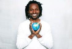 Ein lächelnder junger Mann hält die Weltkugel in seinen Händen Stockfoto