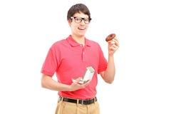 Ein lächelnder Kerl, der rotes T-Shirt trägt und einen Krapfen isst Stockbild