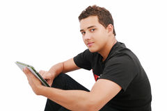 Ein lächelnder Mann, der auf dem Fußboden mit einer Tablette sitzt Stockbilder
