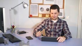 Ein lächelnder Mann, der die Kamera sitzt in seinem Büro betrachtet stock footage