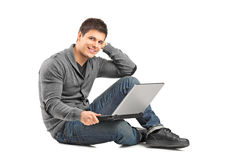 Ein lächelnder Mann mit einem Laptop, der Kamera betrachtet Lizenzfreies Stockbild