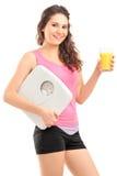 Ein lächelnder weiblicher Athlet, der eine Gewichtsskala und ein Glas ora anhält stockbilder