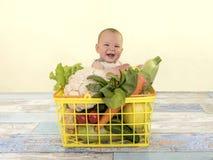 Ein lächelndes Baby im Korb mit Gemüse Stockfoto