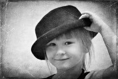 Ein lächelndes kleines Mädchen, das einen schwarzen Hut trägt stockfotografie
