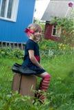 Ein lächelndes kleines Mädchen, das Pippi Longstocking darstellt und auf einem alten Koffer nahe einem Landhaus sitzt Stockfoto