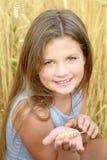 Ein lächelndes kleines Mädchen, das Roggen hält, nageln an Hand fest Goldenes Roggenfeld am Sommertag Konzept der Reinheit, Wachs Lizenzfreies Stockfoto