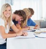 Ein lächelndes Mädchen betrachtet die Kamera, während ihre Freunde studieren Lizenzfreies Stockfoto