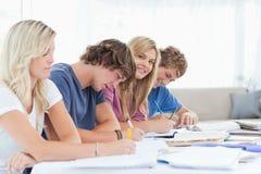 Ein lächelndes Mädchen betrachtet die Kamera, während sie mit Studenten sitzt Stockfoto