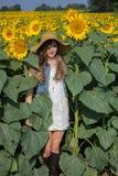 Ein lächelndes Mädchen, das auf einem Gebiet von großen Sonnenblumen sich versteckt Stockfotos