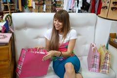 Ein lächelndes Mädchen, das auf einem Sofa nahe bei ihren Einkaufstaschen auf einem Shophintergrund sitzt Ein Mädchen, das ihre K Stockbild