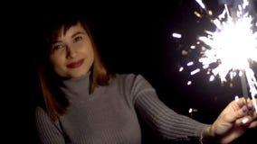 Ein lächelndes Mädchen in einer grauen Strickjacke bewegt seine Hand mit einer Wunderkerze auf einem schwarzen Hintergrund stock video