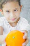 Ein nettes Mädchen gibt eine Orange Lizenzfreie Stockbilder