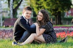 Ein lächelndes Paar, das auf dem Gras sitzt Stockbilder