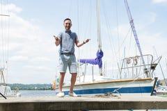 Ein lächelndes Sportseglerporträt auf Pier mit beiden Daumen oben Fluss und Yachten auf Hintergrund Junger erfolgreicher Mannseem lizenzfreie stockfotos