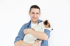 Ein l?chelnder gut aussehender Mann, der einen reinrassigen Hund auf einem wei?en Hintergrund h?lt Das Konzept von Leuten und von stockbild