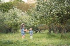 Ein lachender Kinderbruder und -schwester, die in einem Wald spielen stockfoto