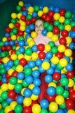Ein lachendes kleines Mädchen, das den Spaß spielt mit Mehrfarbenplastikbällen hat lizenzfreie stockfotos