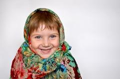 Ein lachendes kleines Mädchen in einem hellen bunten Schal Stockfotografie