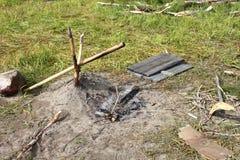 Ein Lagerfeuerplatz mit Katapult für das Kochen und Materialien für das Anzünden auf einem Picknick Stockfotos