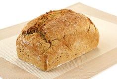 Ein Laib des Brotes auf einem strukturierten Tellersegment stockfotografie