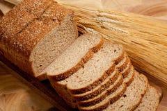 Ein Laib des Brotes und Schlag des Weizens auf Holz Stockfotografie