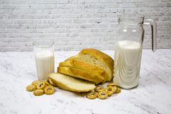 Ein Laib des Weißbrots schnitt mit einem Dekantiergefäßglas Milch gegen ein weißes Marmorbrett stockfotos